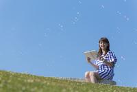 ベンチに座って本を読む笑顔の女性