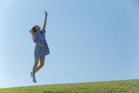 草原をジャンプする女性 11019033705| 写真素材・ストックフォト・画像・イラスト素材|アマナイメージズ