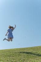 草原をジャンプする女性