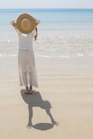 砂浜で麦わら帽子を前に差し出す女性
