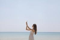 海辺でスマートフォンで撮影する女性
