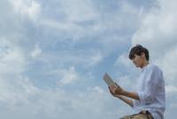 青空の下でタブレットPCを操作する男性 11019033888| 写真素材・ストックフォト・画像・イラスト素材|アマナイメージズ