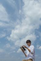 青空の下でタブレットPCを操作する男性