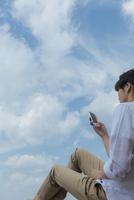 青空の下でスマートフォンを見る男性