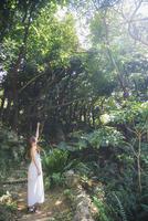 森の中で手を伸ばす女性