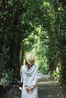 麦わら帽子をかぶる女性の後ろ姿