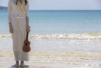 海辺でウクレレを持つ女性