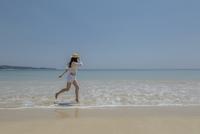 波打ち際を走る女性