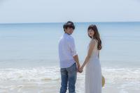 波打ち際で手をつなぐカップル 11019033999| 写真素材・ストックフォト・画像・イラスト素材|アマナイメージズ