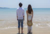 波打ち際に立つカップルの後姿