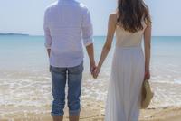 波打ち際で手をつなぐカップルの後姿