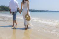 波打ち際を歩くカップルの後姿 11019034006| 写真素材・ストックフォト・画像・イラスト素材|アマナイメージズ