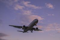 夕暮れ空と着陸する飛行機