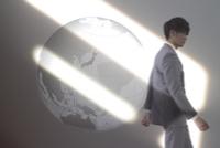 歩くビジネスマンと地球と光 CG
