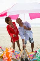 Man and woman setting up beach umbrella