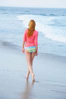 Woman walking on beach (rear view)