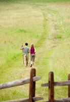 Couple walking in field near wooden gate