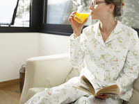woman in pajama drinking orange juice