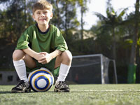 Boy sitting on soccer ball