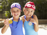 Girls in swimming wear holding medals