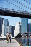 Couple walking under Brooklyn Bridge