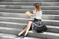 Young woman reading and eating on steps 11021001115| 写真素材・ストックフォト・画像・イラスト素材|アマナイメージズ