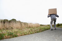 Man carrying cardboard box on road