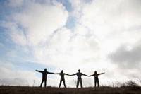 Four people holding hands in field