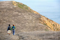Man and woman hiking near cliff