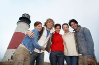 Five people hugging by lighthouse
