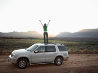 Woman raising arms on roof of car