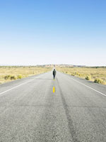 Man walking on centerline of rural road