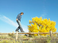 Man walking on wooden fence