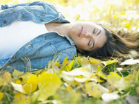 Woman sleeping on autumn leaves