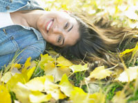Woman lying on autumnal leaves