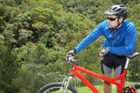 Male cyclist leaning on mountain bike