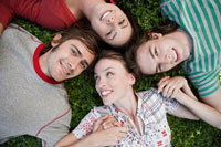 Four friends lying on grass
