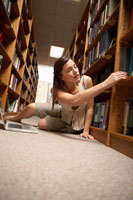 Teenage girl studying on library floor