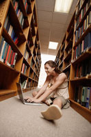 Student using computer on library floor
