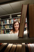 Student behind bookcase in library