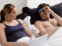 Man looking at girlfriend with laptop