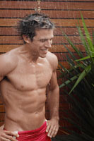 Young man taking shower outdoors