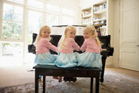 Triplets playing piano in living room