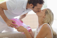 Man kissing and giving present to woman