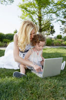 Mother and daughter using laptop in park