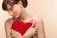 Woman holding heart shaped chocolate box