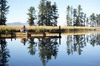 Teenage boy playing guitar by lake