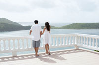 Young couple looking at ocean on balcony