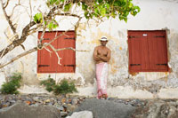Young man in sarong and hat by old house