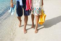 Couple walking on sandy beach 11021004565| 写真素材・ストックフォト・画像・イラスト素材|アマナイメージズ